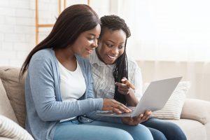 Cheerful black women browsing dating website on laptop
